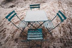 Lijst en stoelen in sneeuw stock afbeelding