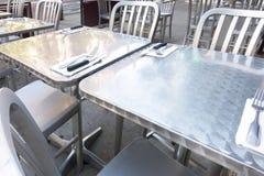 Lijst en stoelen van het roestvrij staal de de openluchtrestaurant royalty-vrije stock afbeelding