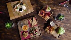 Lijst in het restaurant met voedsel, mening vanaf de bovenkant Snacks op een houten lijst met een mooie textuur heerlijk stock videobeelden