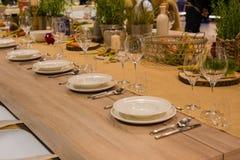 Lijst in het restaurant voor verscheidene personen met glazen en platen wordt gediend die Stock Fotografie