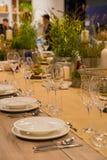 Lijst in het restaurant voor verscheidene personen met glazen en platen wordt gediend die Stock Afbeeldingen