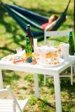 Lijst met flessen bier en voedsel op de partij van de de zomertuin stock fotografie