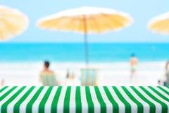 Lijst met gestreept tafelkleed op vage strandachtergrond die wordt behandeld stock afbeelding