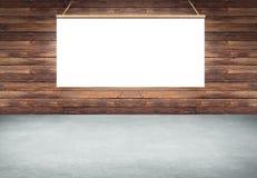 Lijst met het hangen van wit afficheteken op houten muur stock foto