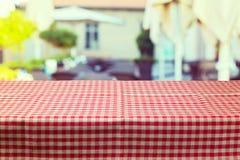 Lijst met rood gecontroleerd tafelkleed over de achtergrond van het onduidelijk beeldrestaurant stock afbeelding