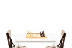 Lijst met schaakbord op het en twee houten stoelen Stock Foto's
