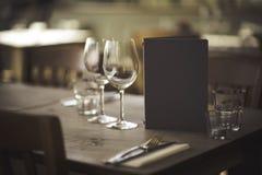Lijst in restaurant met glas en menu stock foto's