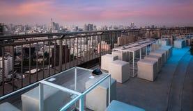 Lijst & stoelen bij terras, stedelijke stadshorizon, Bangkok, Thailand stock foto
