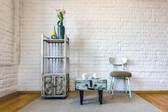 Lijst, stoelen, planken aangaande de achtergrond van een witte bakstenen muur in uitstekend zolderbinnenland royalty-vrije stock fotografie