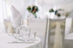 Lijst voor een van het gebeurtenispartij of huwelijk ontvangst op wit tafelkleed wordt geplaatst dat Witte zachte achtergrond met Royalty-vrije Stock Afbeeldingen