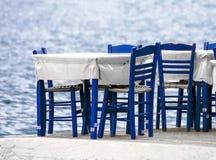 Lijsten en blauwe stoelen door de kust Griekenland royalty-vrije stock fotografie