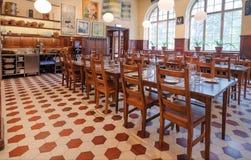 Lijsten en houten stoelen in leeg restaurant Kvarnen met vensters en uitstekend meubilair Royalty-vrije Stock Foto's