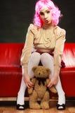 Lik ett barn kvinna och nallebjörn som sitter på soffan Fotografering för Bildbyråer