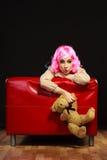 Lik ett barn kvinna och nallebjörn som sitter på soffan Arkivbilder