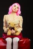 Lik ett barn kvinna och nallebjörn som sitter på soffan Arkivfoto