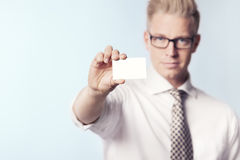Likable businessman showing white blank card. Stock Photos