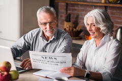 Likable old couple reading newspaper at the kitchen table Royalty Free Stock Photos