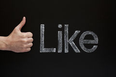 Like. Thumbs up infront of a blackboard with the word Like written with white chalk on it Royalty Free Stock Photography