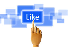 Like button. Wooden finger pressing a like button stock photo