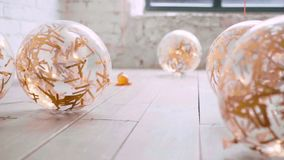Like cat slowly and carefully sneaking up to its goal, transparent balloons lie on light wooden floor, golden shiny