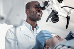 Positive delighted international dentist examining his patient stock image