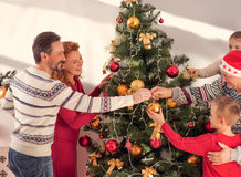 We like decorating Christmas tree together. Happy New Year. Joyful family is standing near fir-tree and hanging toys. They are smiling happily Royalty Free Stock Photo