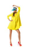 Like A Doll. Fashion model posing in red high heels, yellow mini dress and blue plastic sun visor. Full length studio shot isolated on white Royalty Free Stock Image