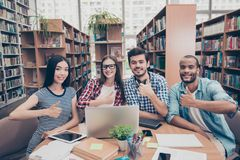 We like education! Successful future for smart youth! Four attractive young bachelors are welcoming in their university`s library. Gesturing thumbups, smiling stock photos