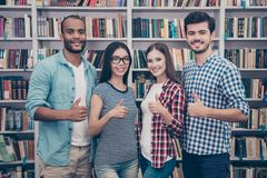 We like education! Successful future for smart youth! Four attra. Ctive young bachelors are welcoming in their university`s library, gesturing thumbups, smiling Royalty Free Stock Images