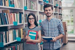 We like education! Successful future for smart youth! Two attractive young bachelors are welcoming in their. University`s library`s archive, holding literature stock images