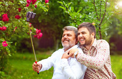 Like father like son. family makes selfie on smartphone Royalty Free Stock Photos