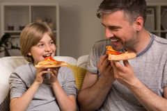 Like father like son. Image of content father and son sitting on a sofa eating pizza Stock Photos