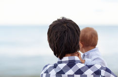 Like father like son. Rearview of a father holding his little baby boy, looking out to the horizon on the ocean Royalty Free Stock Image