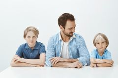 Like father like sons. Portrait of beautiful happy family sitting with hands together, dad looking at cute son and. Smiling broadly while waiting for mom royalty free stock images
