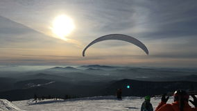 Almost like floating in space. MOSCOW RUSSIA - 01.01.2017: male athlete flying from the mountain on a hang-glider or paraglider. Snow Mountain, near snowboarders stock video