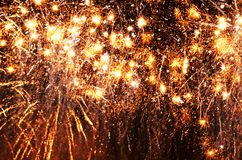 Gold shooting stars lights up black dark night sky background. Like gold shooting stars lighting up the black sky are these sparkling golden showers of fireworks stock images