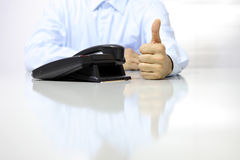 Like hand with office phone on desk Stock Images