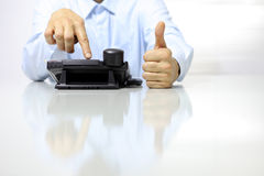 Like hand with office phone on desk Royalty Free Stock Photos