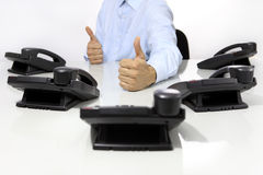 Like hand with office phones on desk Stock Image