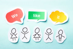 We like it. Happy paper people with speech bubbles of We like it text on the blue background stock photo