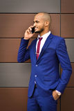 He like his work.Happy smiling cheerful successful businessman speak by phone,approves new project. African important,young,successful,smiling businessman stock photos