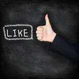 Like - likes thumbs up on chalkboard. LIKE written on blackboard with hand giving thumbs up hand sign gesture. Black blackboard texture background icon Royalty Free Stock Photo