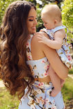 Like mother like daughter. beautiful family in similar dresses. Fashion outdoor photo of beautiful family look.beautiful mother with long dark hair posing with Stock Photography
