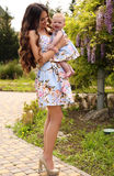 Like mother like daughter. beautiful family in similar dresses. Fashion outdoor photo of beautiful family look.beautiful mother with long dark hair posing with royalty free stock photo