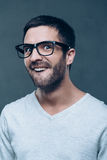Like a nerd. Young nerd man in eyeglasses making a face while standing against grey background royalty free stock image