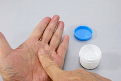 Like paint a topical cream for roughed his hands. Like a painting a topical cream for roughed his hands Stock Photo