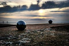 Almost like playing boule by the beach. Found these round balls and wanted to create life in big verses small dimension royalty free stock photos