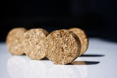 Like a rolling stone - Macro details on black and white. Like rolling stones, cut cork slices on a white tabletop. On a quite black background royalty free stock image