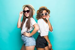 Like a sisters. Two beautiful young girl friends in sunglasses and straw hat posing with smile and have a fun on blue background stock images