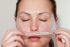 Like a snake. Woman removes cucumber mask like a snake changes skin Stock Image